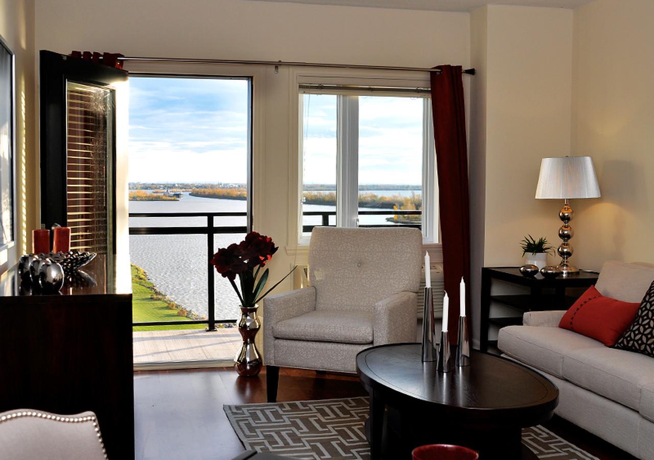 Salon d'un appartement avec balcon donnant sur le fleuve Saint-Laurent