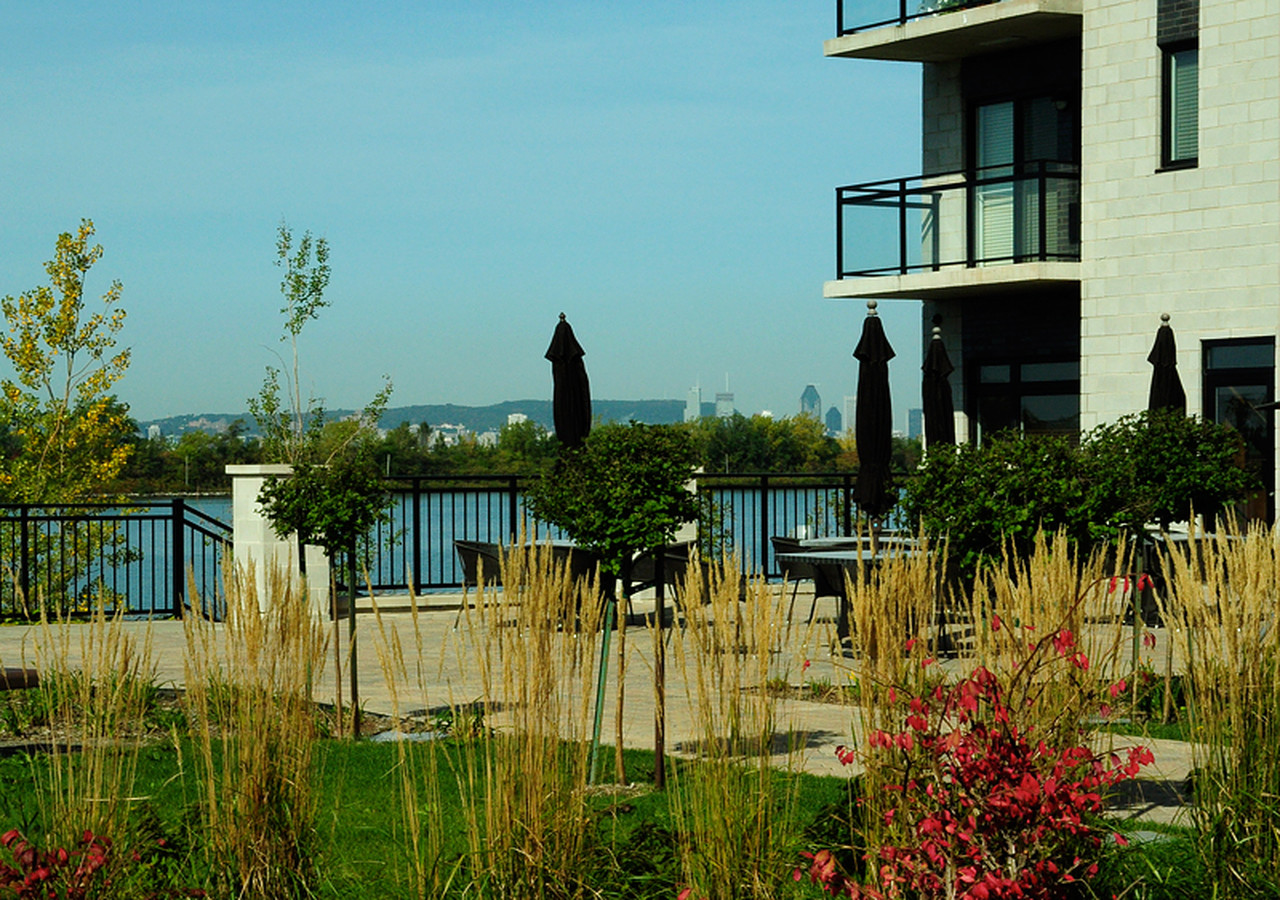 Côté du bâtiment avec grande terrasse et vue sur le fleuve et la ville de Montréal.