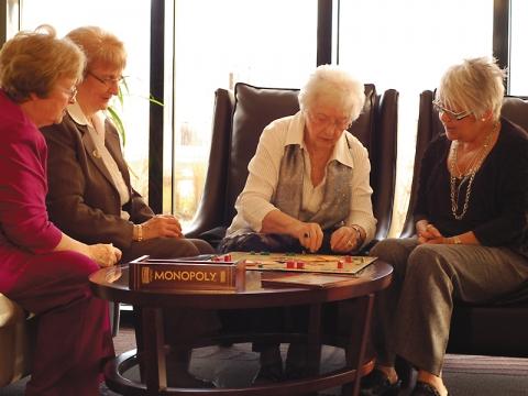 Quatre femmes qui jouent au monopoly dans un salon confortable